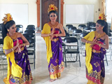 黄色と紫が鮮やかなバリダンスの衣装を着た3人の女性が合掌のポーズをとっている。